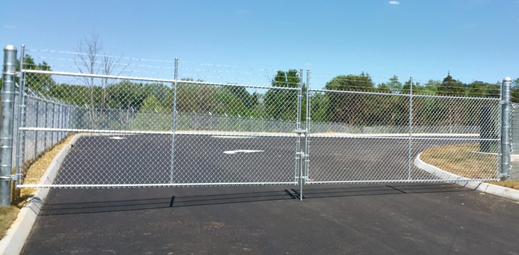 Chain link double swing gate with barb wire and drop rod