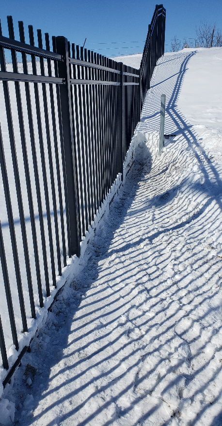 An ornamental gate and fence caked in snow