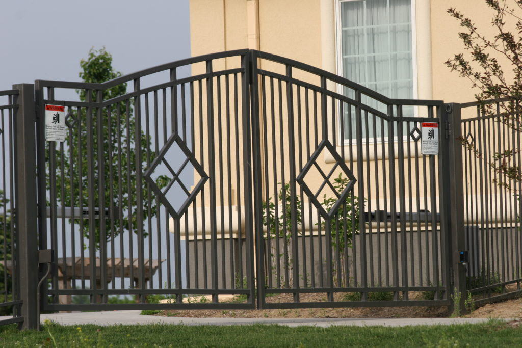 Double swing drive way gate in front of a residential house with automated gate access controls