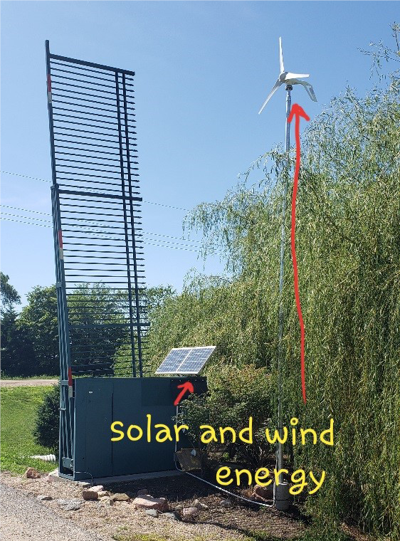Automated gate with a solar panel and windmill for energy supply