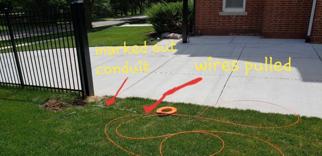 A completed driveway with marks shown of where the conduit and pulled wires lay