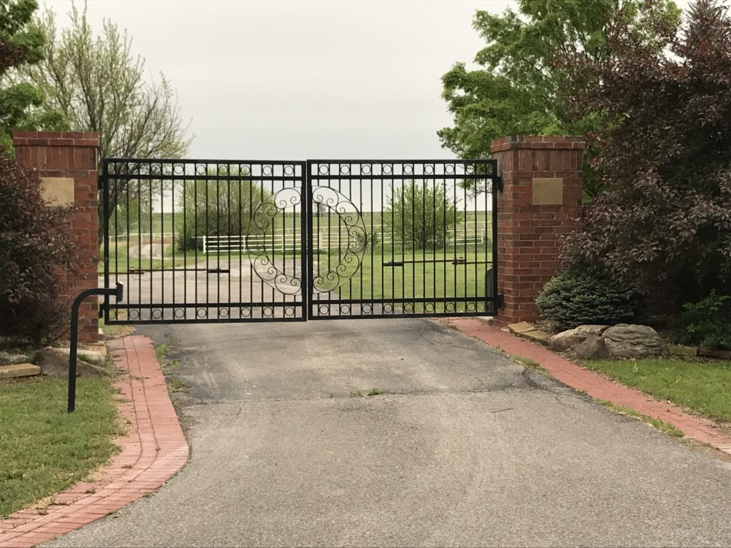 Ornamental automated swing gate installed in front of a driveway with keypad access
