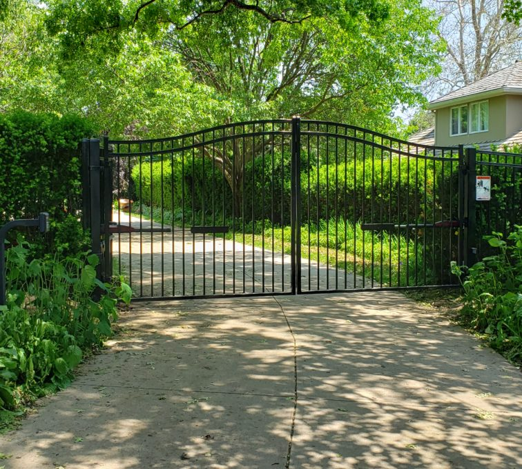 Arched automatic swing gate in front of a driveway