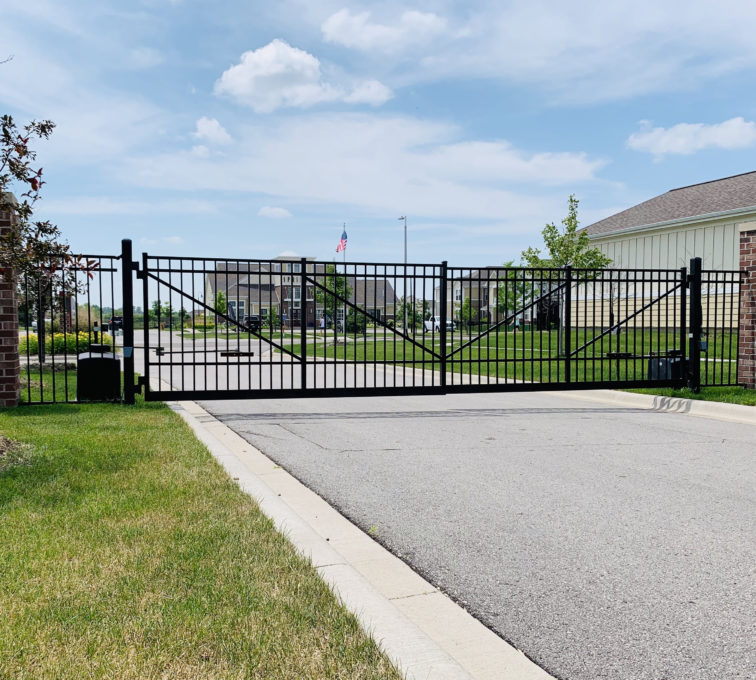 Closed black ornamental automatic double swing gate with operators.  access control commercial gate installation company automated electric gate opener operators solar motor motorized automatic access control driveway estate slide swing rolling cantilever vertical lift vertical pivot open close stop key pad switch push button three button control intercom call button telephone entry computerized entry loop exit obstruction shadow detector transmitter receiver radio frequency wifi box cantilever aluminum